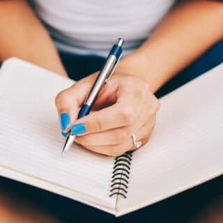 A woman wiht blue nails and a diamond ring on her middle finger writing in a spiral notebook in her lap with a steel pen.