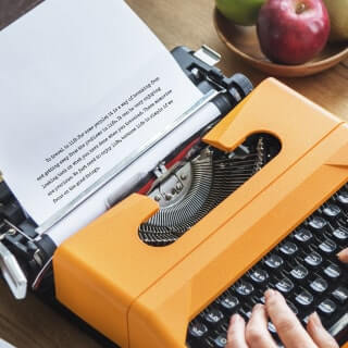 Fingers typing on a vintage orange typewriter near to a bowl of apples.